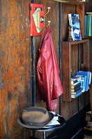 DIY coat peg made from books and hook next to bookshelves on rustic wooden wall