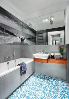 Grey walls and black and white photo mural reflected in mirror; monochrome colour scheme in bathroom combined with Oriental, blue tiled floor