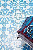 Oriental tile mosaic on bathroom floor; jewellery on towels on stool