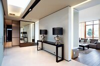 Classic lamps on console table in minimalist corridor with mirror and sliding door; view of seating area in interior