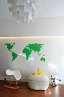 Classic child's rocking chair and toys on designer trunk against wall with indirect lighting and mural of green work map