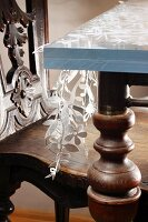 Antique wooden chair and creative table structure; floral motif cut out of fabric sandwiched between two glass panels on steel structure with turned wooden legs