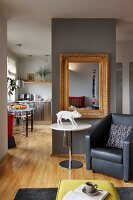 Leather armchair, pig sculpture on round table and antique mirror on partition screen kitchen-dining room in background