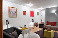 Youthful, artistic living area with couch, cubic tables and modern artworks on wall; pig sculpture on round table in foreground