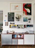 Sideboard with galvanised and white metal doors below shelving units and posters on wall
