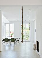 Green shell chairs and climbing rope hanging from ceiling in minimalist, white dining room