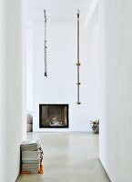 Climbing ropes hung from ceiling in front of fireplace integrated in wall of modern interior