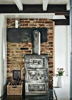 Industrial-style wood-burning stove against old brick wall