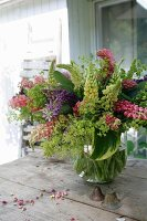 Luxuriant bouquet of lupins in glass vase and vintage metal bells on rustic wooden table