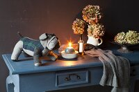 Candle, soft toy and hydrangeas on grey console table