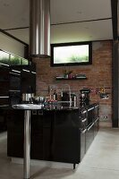 Black free-standing designer kitchen counter below cylindrical stainless steel extractor hood in front of brick wall