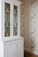 White vintage dresser and patterned wallpaper