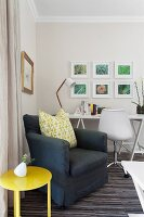 Dark grey armchair & yellow side table in front of work area with white desk & swivel chair