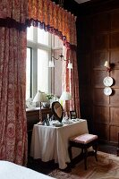 Dressing table below window with toile-de-jouy curtains and decorative china wall plates on wood-panelled walls in bedroom