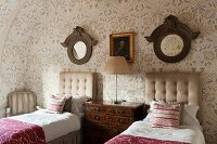 Twin beds with button-tufted headboards, antique chest of drawers, round mirrors with wooden frames and floral wallpaper in attic bedroom in English manor house