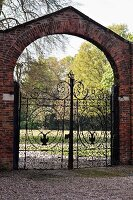 Ornate wrought iron gate in brick wall with rounded arch leading to park