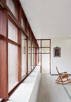 Purist interior of modern, Indian house with stone floor and continuous strip of wood-framed windows