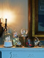 Snow globes with festive motifs in front of gilt-framed mirror on mantelpiece