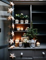 Candles, flowering plants and star-shaped fairy lights arranged on dark grey dresser