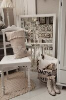 Hessian sack on white-painted kitchen chair, vintage ladies' laced boots and vintage-style flea-market finds on white-painted wooden floor