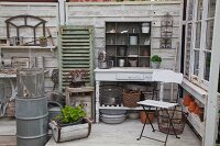 White folding chair and rustic console table with plant pots on lower shelf in shed