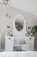 White dressing table with oval mirror against wall painted pastel grey in bedroom