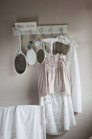 Vintage clothing and hand mirrors hanging from row of hooks