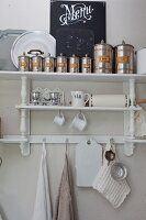 Metal storage tins on top of white-painted shelves