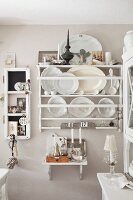 White decorative plates and platters in plate rack on pastel wall in rustic kitchen