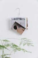 Magazine tack made from wire coat hanger on wall
