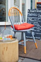 A newly painted grey and orange Windsor chair with an orange cushion in front of a restaurant