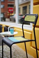 A modern black chair with a woven pattern on the seat and the back