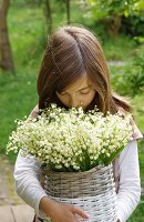 Girl outdoors holding large bouquet of lily-of-the-valley in wicker basket