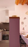 Counter with pastel lilac body between kitchen and dining areas