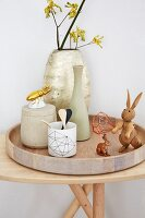 An arrangement featuring vases, wooden rabbits and gilded porcelain beetles on a wooden tray on a wooden table