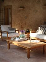 Outdoor sofa set and wooden coffee table on terrace with terracotta tiles