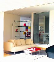 Set of coffee tables and pale sofa in front of workspace behind glass panel and shelves fitted in aperture