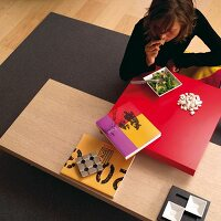 Woman eating at low table with red tabletop above wooden surface