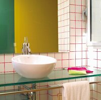 Washstand with white china basin on glass counter against white-tiled wall with red grouting