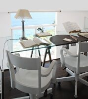 Glass tabletop on trestles and wooden swivel chairs in workspace on gallery; view of sea through glass balustrade