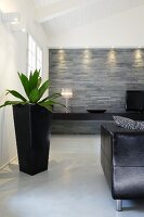 Black planter on floor, partially visible leather couch, illuminated stone wall and low, floating black sideboard