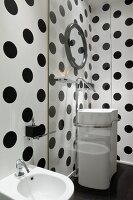 View through glass screen of white washstand with floor-mounted taps against black and white polka dot walls