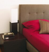 Magenta bed linen on bed upholstered in warm taupe next to cubic black and white lamp on dark, cubic bedside table