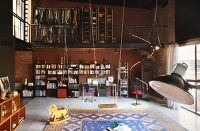 Double-height loft interior with bookcase and desk below open-fronted wardrobes on mezzanine; swing in foreground next to rocking horse on large rug