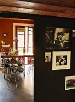 View past souvenir photos on black partition to metal bar stools at breakfast bar in kitchen