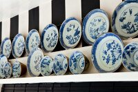 Collection of blue and white plates and bowls on wooden shelves on wallpaper with wide stripes