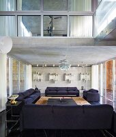 Dark sofa set below exposed concrete ceiling with classic pendant lamp in modern interior with view of room in upper storey