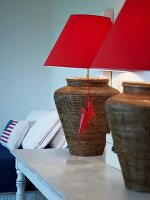 Lamps with rattan bases and red lampshades on antique table