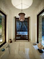 Pattern of light and shadow thrown by wicker lampshade above plunge pool surrounded by windows