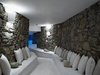 Lounge area between rough stone walls with white-painted masonry benches on both sides and bright wall lamps